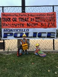 Kids in Construction Costumes in Front of Recreation and Police Banners